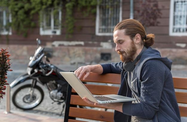 Vista lateral do homem com o laptop na cidade