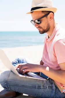 Vista lateral do homem com o laptop na praia