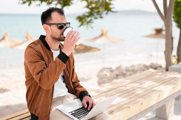 Vista lateral do homem com óculos de sol, tomando café na praia e trabalhando no laptop