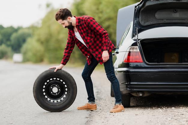 Vista lateral do homem com pneu sobressalente
