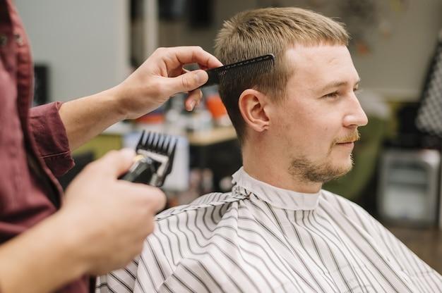 Vista lateral do homem cortando o cabelo