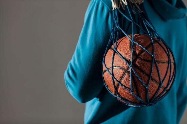 Vista lateral do homem de capuz segurando basquete na net