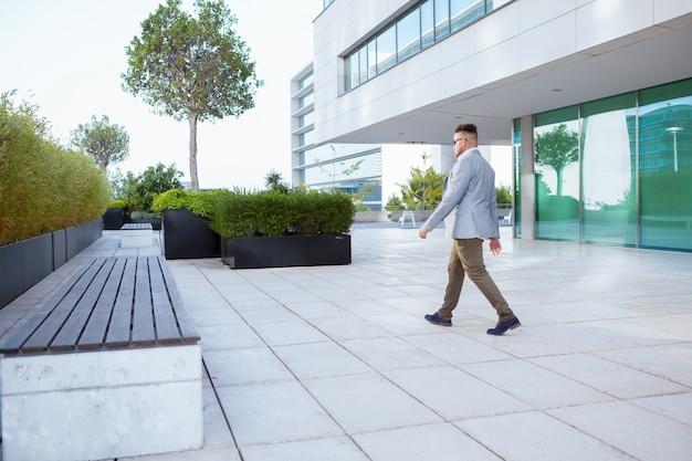 Vista lateral do homem de negócios andando ao ar livre