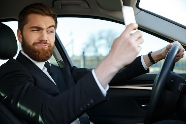 Vista lateral do homem de negócios barbudo fazendo selfie
