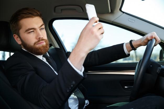 Vista lateral do homem de negócios calmo fazendo selfie