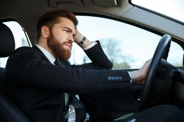 Vista lateral do homem de negócios cansado dirigindo carro