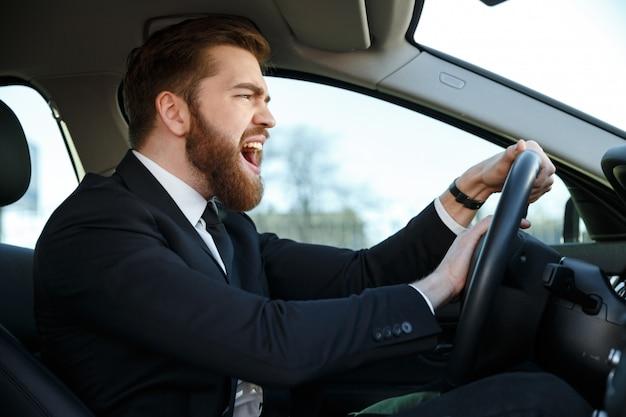 Vista lateral do homem de negócios com raiva dirigindo e apita
