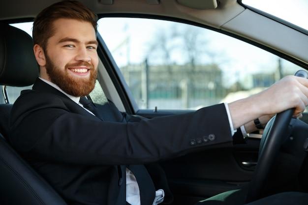 Vista lateral do homem de negócios feliz sentado ao volante