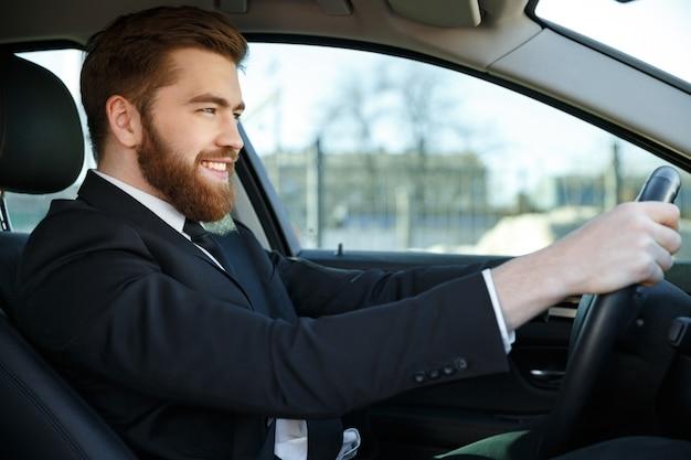 Vista lateral do homem de negócios sorridente, sentado ao volante