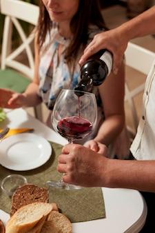Vista lateral do homem derramando vinho em vidro na mesa de jantar