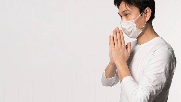 Vista lateral do homem doente com máscara médica rezando