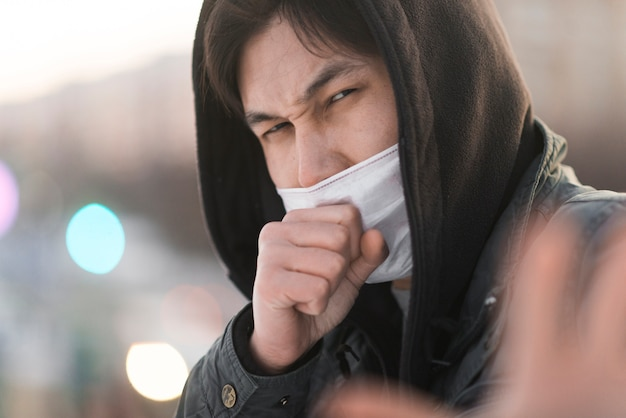 Vista lateral do homem doente tossindo