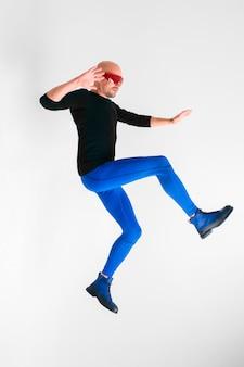Vista lateral do homem elegante de óculos vermelhos futuristas e meia-calça azul, deitado no ar