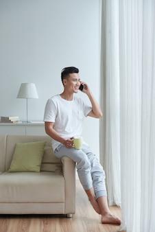Vista lateral do homem empoleirar-se no braço do sofá falando ao telefone e olhando pela janela