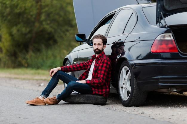 Vista lateral do homem encostado no carro