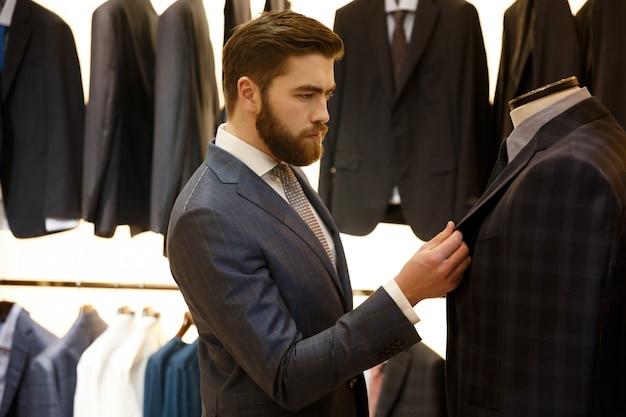 Vista lateral do homem escolhendo uma jaqueta na loja Foto gratuita