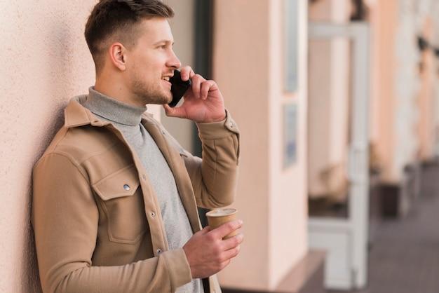 Vista lateral do homem falando ao telefone