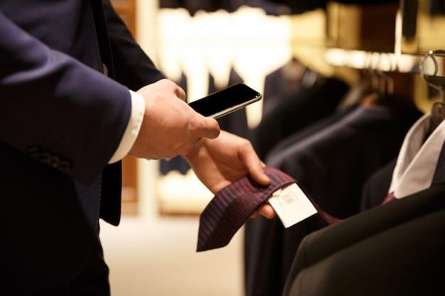 Vista lateral do homem fazendo foto da lista de preços