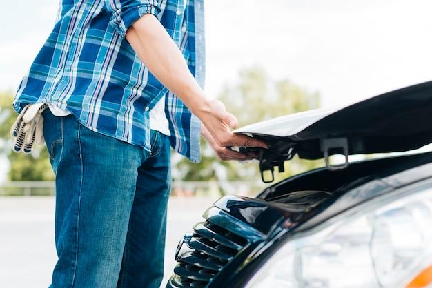 Vista lateral do homem fechando o capô do carro