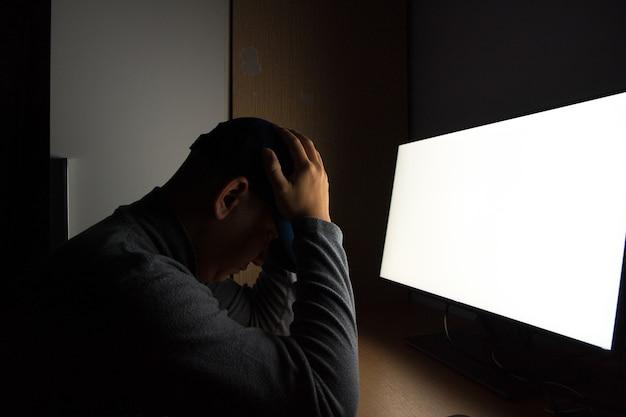 Vista lateral do homem hacker sentar no monitor do computador. no quarto escuro.