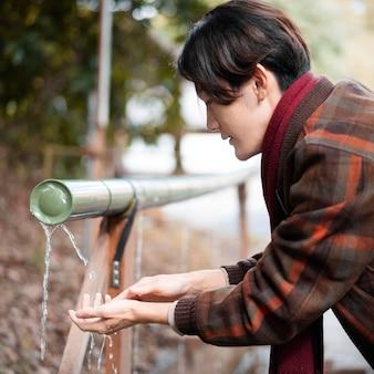 Vista lateral do homem lavando as mãos ao ar livre