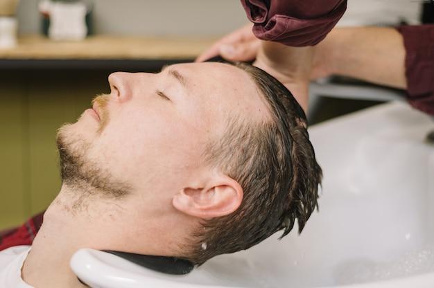 Vista lateral do homem lavando o cabelo na barbearia