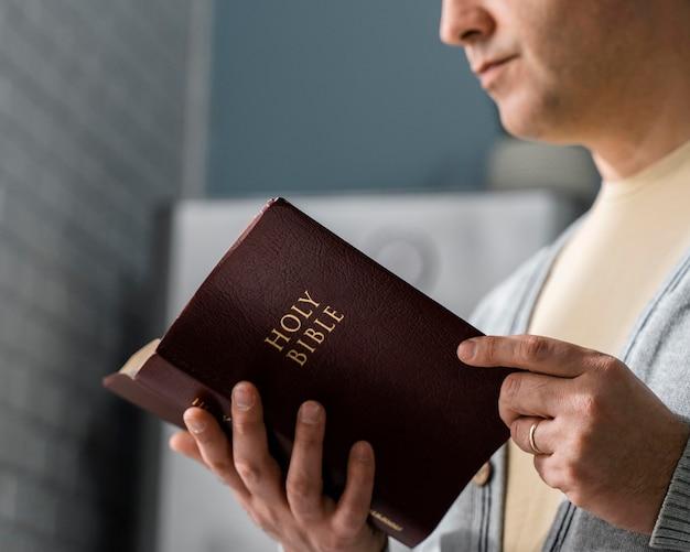 Vista lateral do homem lendo a bíblia
