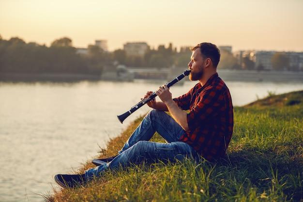 Vista lateral do homem loiro barbudo caucasiano bonito na camisa xadrez, sentado no penhasco e tocando clarinete.