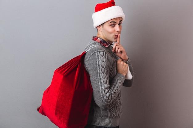 Vista lateral do homem misterioso com suéter e chapéu de natal segurando uma sacola com presentes enquanto mostra o gesto de silêncio e olhando
