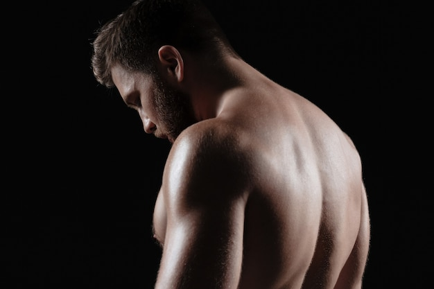 Vista lateral do homem musculoso nu. fundo escuro isolado