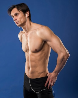 Vista lateral do homem musculoso sem camisa usando fones de ouvido