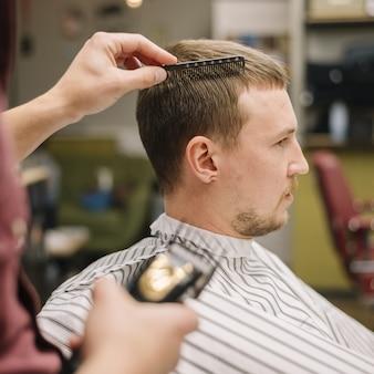 Vista lateral do homem na barbearia