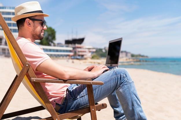 Vista lateral do homem na cadeira de praia, trabalhando no laptop