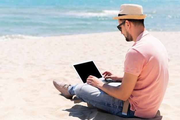 Vista lateral do homem na praia com óculos de sol, trabalhando no laptop
