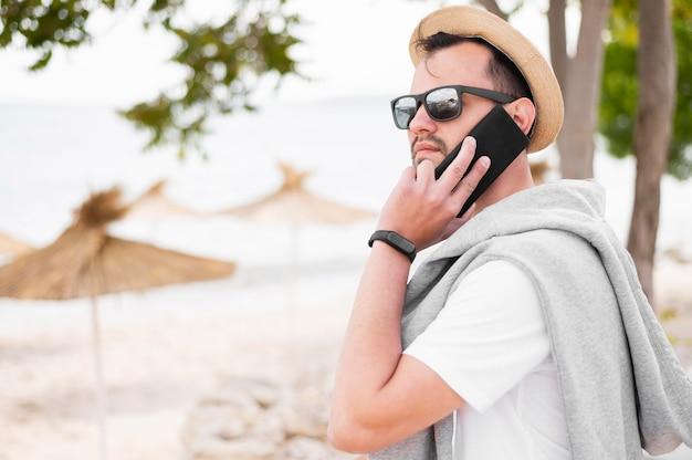 Vista lateral do homem na praia falando no smartphone