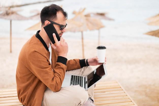Vista lateral do homem na praia trabalhando enquanto tomando café