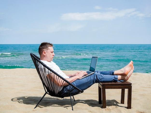 Vista lateral do homem na praia trabalhando no laptop