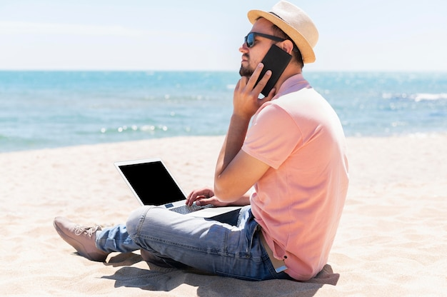 Vista lateral do homem na praia trabalhando