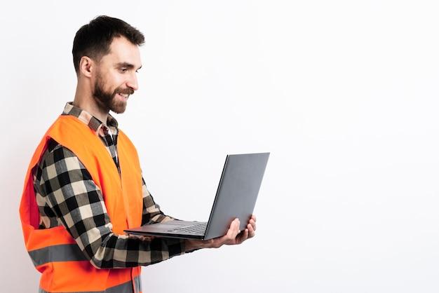 Vista lateral do homem no colete de segurança segurando laptop