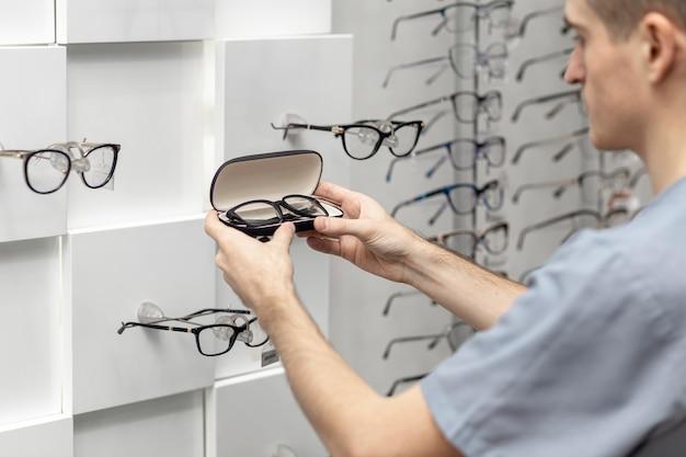 Vista lateral do homem olhando par de óculos nas mãos