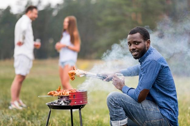 Vista lateral do homem participando do churrasco para os amigos