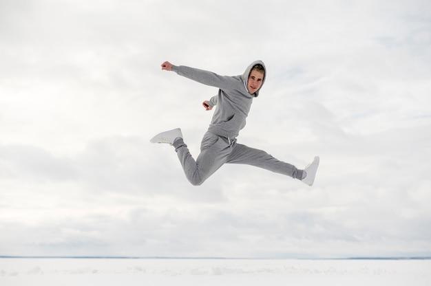 Vista lateral do homem posando enquanto dança lá fora
