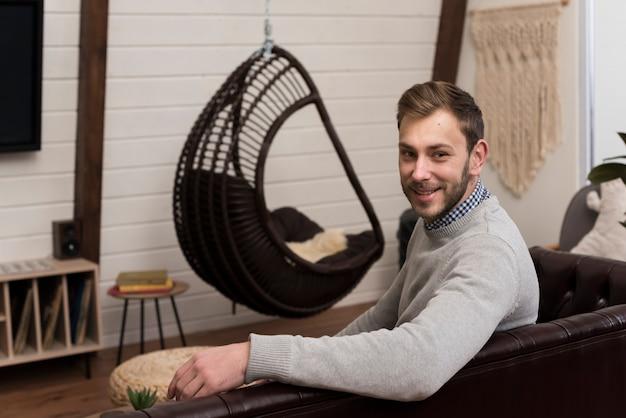 Vista lateral do homem posando no sofá em casa
