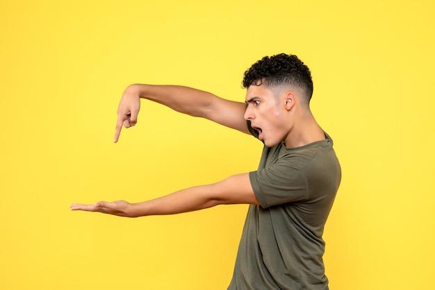 Vista lateral do homem que o cara chocado aponta o dedo para sua palma
