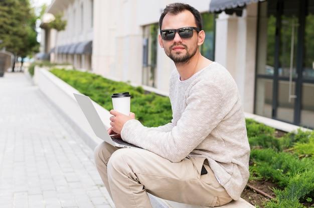 Vista lateral do homem que trabalha fora com laptop e café
