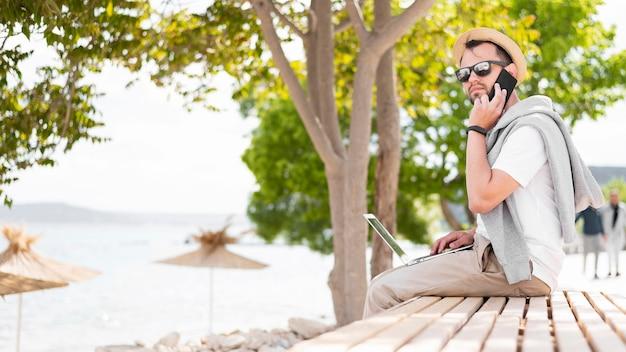 Vista lateral do homem que trabalha na praia com laptop e smartphone
