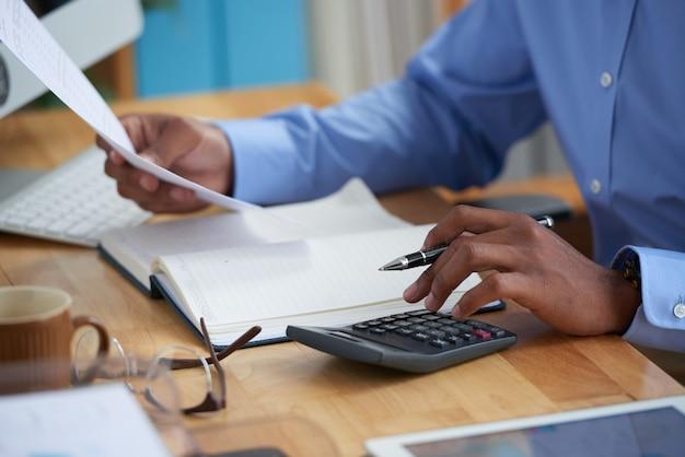 Vista lateral do homem recortado trabalhando no relatório financeiro