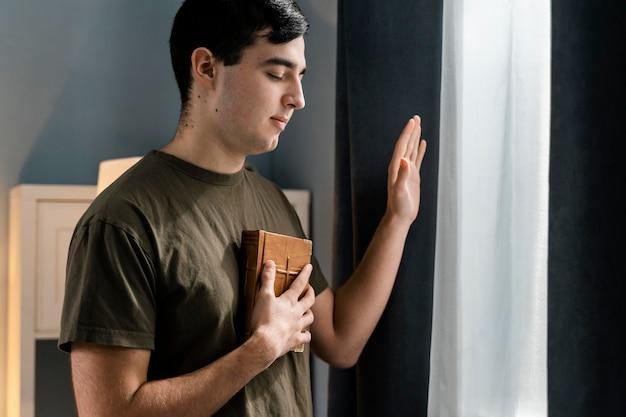 Vista lateral do homem segurando a bíblia enquanto está sentado ao lado da janela