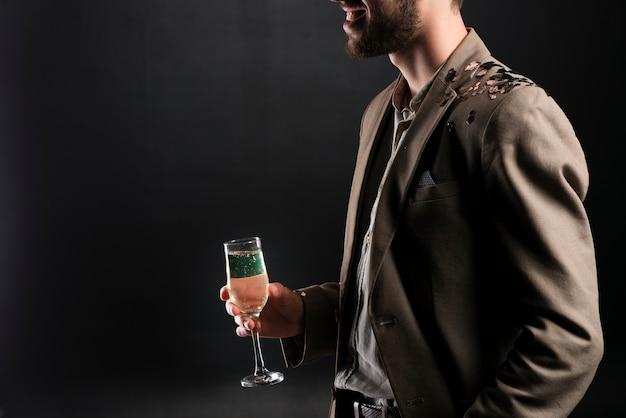 Vista lateral do homem segurando a taça de champanhe