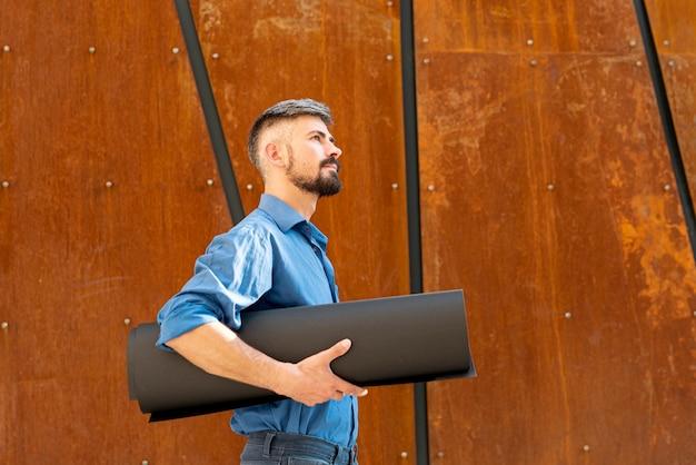 Vista lateral do homem segurando esquemas de construção